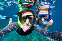 Couple snorkeling. Underwater photo of a young couple snorkeling at tropical ocean Stock Image