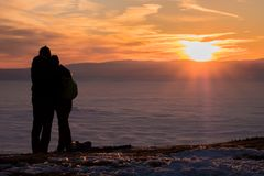 Couple on mountain looking over low stratus to beautiful sunset. Couple on snow covered mountain Schoeckl looking over city Graz under low stratus to mountain Stock Photography