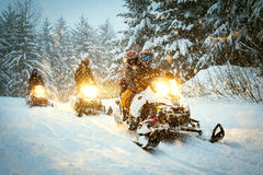 Couple snow mobile in snow storm stock images