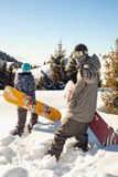 Couple snowboarder goes through deep snow in the mountain Royalty Free Stock Images