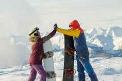 Free Couple Snowboarding Freeriders Man And A Woman Give Five With Snowboards Stock Photography - 128050832