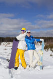 Couple with snowboards in their hand standing on a hillside. Pretty couple with snowboards in their hand standing on a hillside, sunny winter day Stock Photos