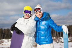 Couple with snowboards in their hands. Portrait of beautiful couple with snowboards in their hands, sunny winter day Stock Image