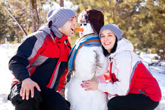 Couple with a snowman Stock Images