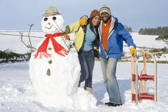 Couple with snowman and sled in snowy field Stock Photos