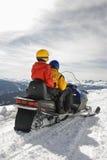 Couple on snowmobile. Man and woman riding on snowmobile in snowy mountainous terrain Stock Photos