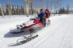 Couple On Snowmobile. Couple driving snowmobile on snow covered track Royalty Free Stock Photo