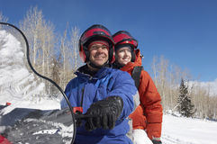Couple On Snowmobile. Happy couple sitting on snowmobile in snow Royalty Free Stock Images