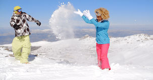 Couple in snowsuits playing the snow Royalty Free Stock Photo