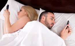 Couple socialising with mobile phones in bed Stock Photography