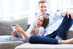 Couple on sofa with digital tablet Royalty Free Stock Images