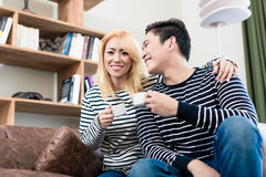 Couple on Sofa drinking coffee together Stock Photography