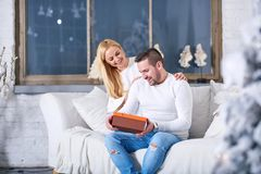 Couple on a sofa giving presents. A beautiful happy young couple sitting on the sofa in the living room with the christmas tree and giving presents to each other stock photography