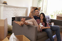 Couple On Sofa Holding Keys Taking A Break On Moving Day Royalty Free Stock Photo