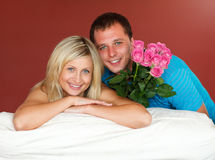 Couple on sofa holding a rose bouquet Stock Image