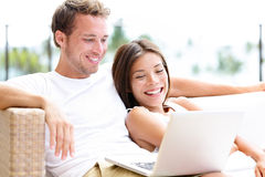 Couple in sofa with laptop pc at home laughing Stock Images