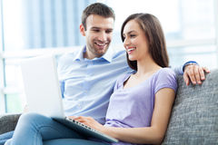 Couple on sofa with laptop Stock Images