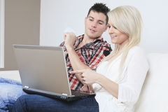 Couple on sofa with laptop who want to buy. A Couple on sofa with laptop who want to buy something on the Internet royalty free stock images