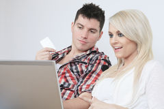 Couple on sofa with laptop who want to buy Royalty Free Stock Photos