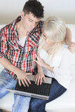 Couple on sofa with laptop who want to buy. A Couple on sofa with laptop who want to buy something on the Internet Stock Photos