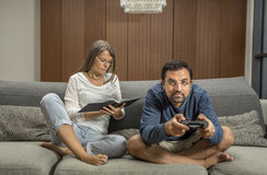Couple on a sofa, man is playing video games while woman reading. Couple on a sofa, men is playing video games while women reading a book in their city apartment Royalty Free Stock Photo