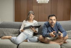 Couple on a sofa, man is playing video games while woman reading. Couple on a sofa, men is playing video games while women reading a book in their city apartment Stock Photos