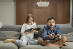 Couple on a sofa, man is playing video games while woman reading. Couple on a sofa, men is playing video games while women reading a book in their city apartment Royalty Free Stock Image