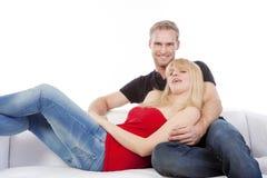 Couple on sofa smiling Stock Photos