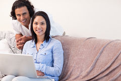 Couple on the sofa surfing the internet Stock Images