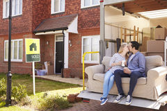 Couple With Sofa On Tail Lift Of Removal Truck Moving Home Stock Photography
