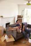Couple On Sofa Taking A Break From Unpacking On Moving Day Stock Photo
