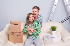 Young Happy Couple On Sofa Taking A Break From Unpacking On Moving Day royalty free stock photos