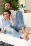 Couple on sofa telephoning Stock Images