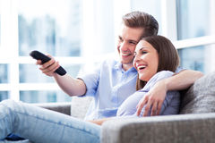 Couple on sofa with TV remote Royalty Free Stock Image