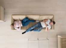 Couple on sofa using mobile phones top view. Top view of Young couple on sofa using a mobile phones Royalty Free Stock Photos