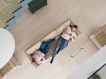 Couple on sofa using mobile phones top view. Top view of Young couple on sofa using a mobile phones Royalty Free Stock Image