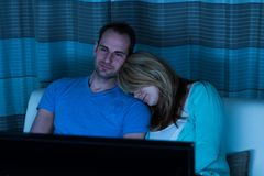 Couple on sofa watching television Stock Photos