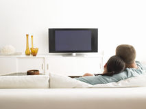Couple On Sofa Watching TV stock images