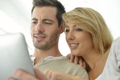Couple in sofa websurfing with tablet Royalty Free Stock Photo