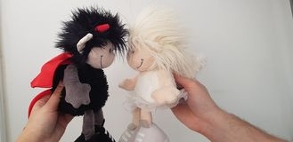a couple of soft toys designed as boy and girl angel and satan going to kiss stock photos