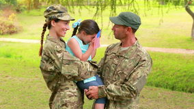 Couple of soldier reunite with their daughter. In park stock video