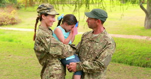 Couple of soldier reunite with their daughter. In park stock footage