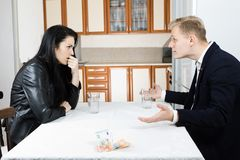 Couple solving financial crisis together on table in kitchen royalty free stock images