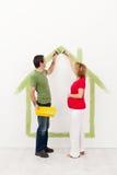 Couple som förväntar en behandla som ett barn - måla deras hem royaltyfri fotografi