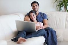 Couple som håller ögonen på en film med en bärbar dator Arkivbild