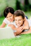 Couple som ligger på gräset med, försilvrar datoren Arkivbilder