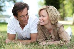 Couple som ligger på gräset arkivbild