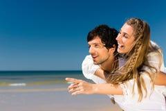 Couple som tycker om frihet på stranden Royaltyfria Foton