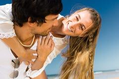 Couple som tycker om frihet på stranden Arkivfoto