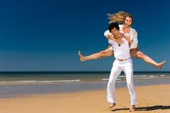 Couple som tycker om frihet på stranden Arkivbild